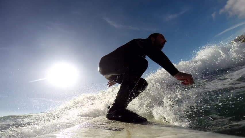 A surfer swiftly riding on the surface of water while maintaining balance, sun visible in the sky, POV | Shutterstock HD Video #8258803