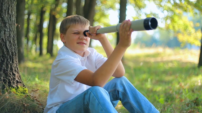 Happy caucasian teenager boy looks through a telescope. Childhood dreams and memories.