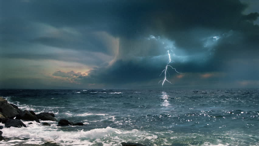 Cinematic storm clouds with lightning strikes reflecting in ocean.