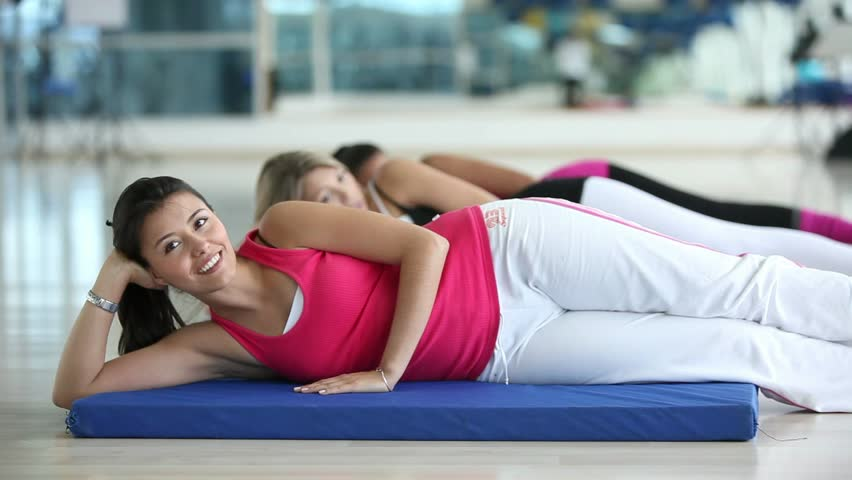 Group of women lying on the floor exercising at the gym  - HD stock footage clip