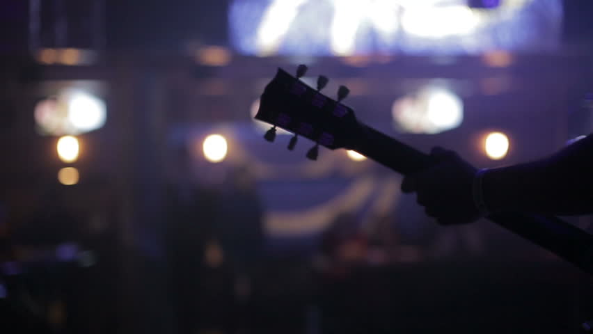 Man lead guitarist playing electrical guitar.Concert rock band performing on stage with singer performer, guitar, drummer. Music video punk, heavy metal or rock group. | Shutterstock HD Video #8268622