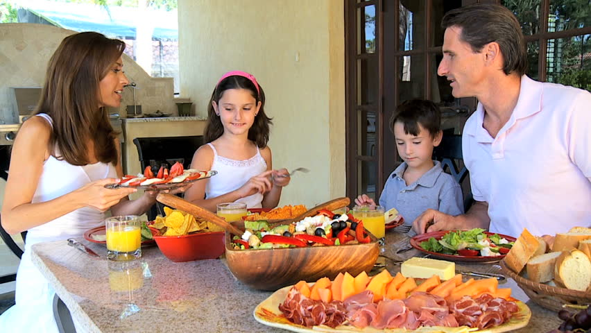 Attractive Caucasian family sitting at home sharing a healthy meal together 60FPS - HD stock video clip