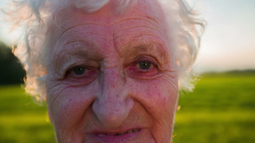 Portrait of an old woman with wrinkles. Slow motion shoot of portrait of an old woman with wrinkles looking to the camera an feeling blessed and relaxed but tired - HD stock video clip