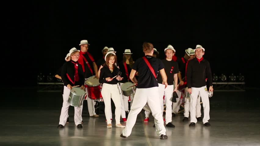 Musical group of fourteen young people in white pants with whistling leader play drums on stage - HD stock footage clip