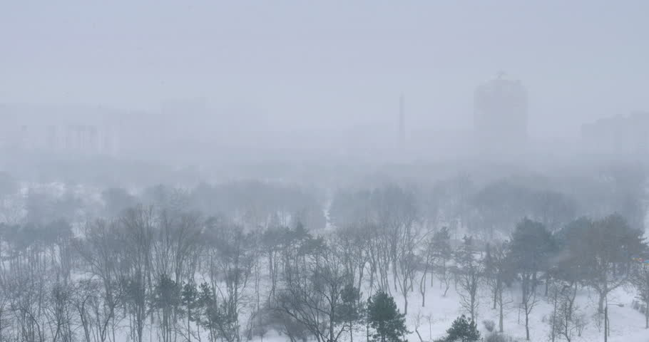 Snow falling in winter park with buildings silhouette on a background. 4K UHD.  - 4K stock footage clip