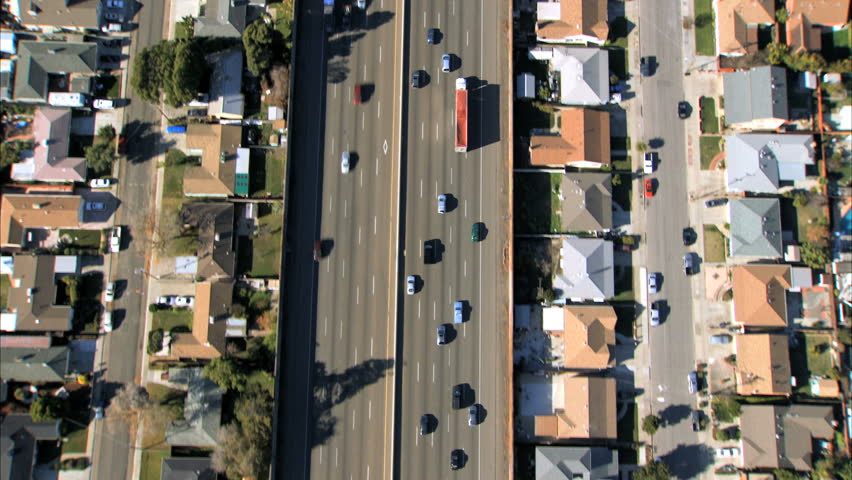 Aerial view following traffic on a freeway with suburban housing either side - HD stock footage clip