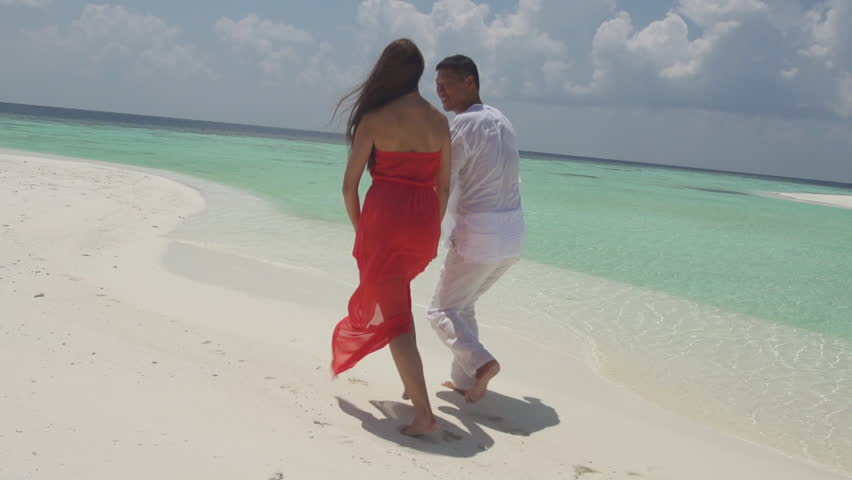Slow Motion Rear View Of Multicultural Couple Jumping Playfully On White Sandy Beach