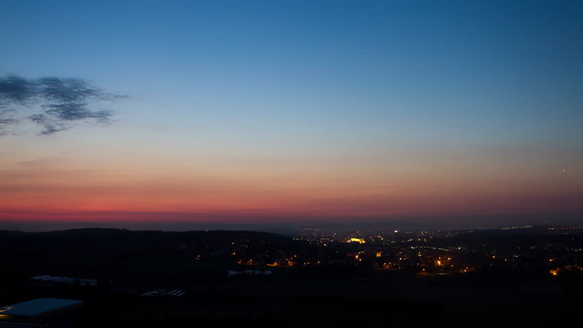 Time lapse clip of a rural area with a city in the background going from night into colourful sunrise.