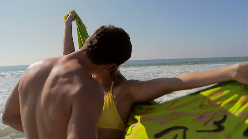 Young couple kissing at ocean's edge with scarf blowing in breeze - HD stock footage clip