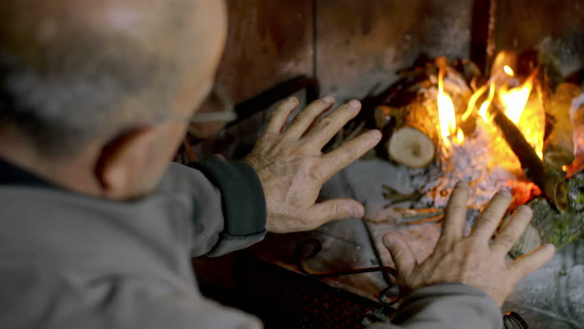 man feeling cold put his hands near the fire in the fireplace: flames, wood - 4K stock footage clip