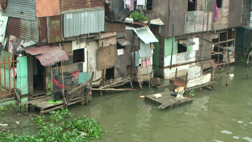 MANILA, PHILIPPINES - OCTOBER 2009: Slum Houses On Bank Of Polluted River In Manila, Philippines