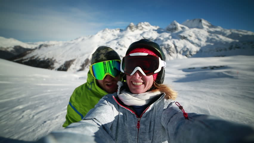 Young happy couple on ski slopes at the top of snow capped mountains taking a selfie using a smart phone making smiles and happy faces.Alps in Switzerland.