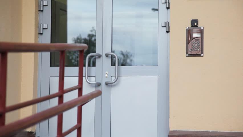 little girl uses entrance door intercom of apartment building