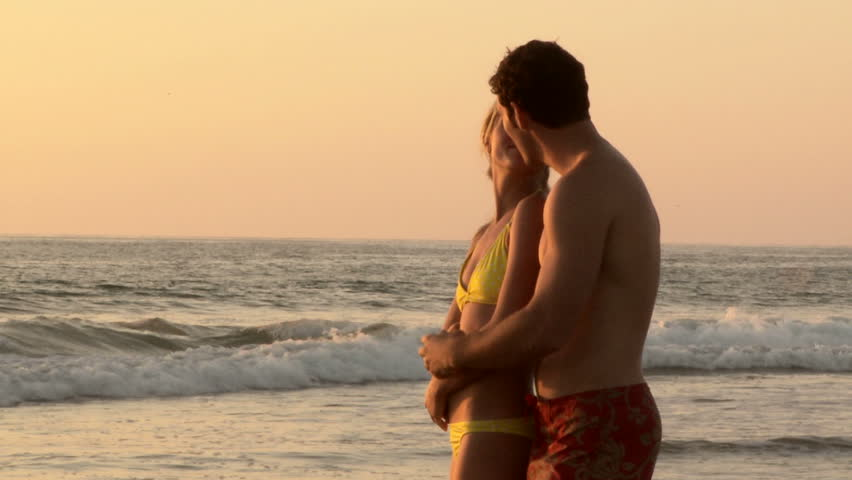 Young couple kissing on beach at sunset | Shutterstock HD Video #854242