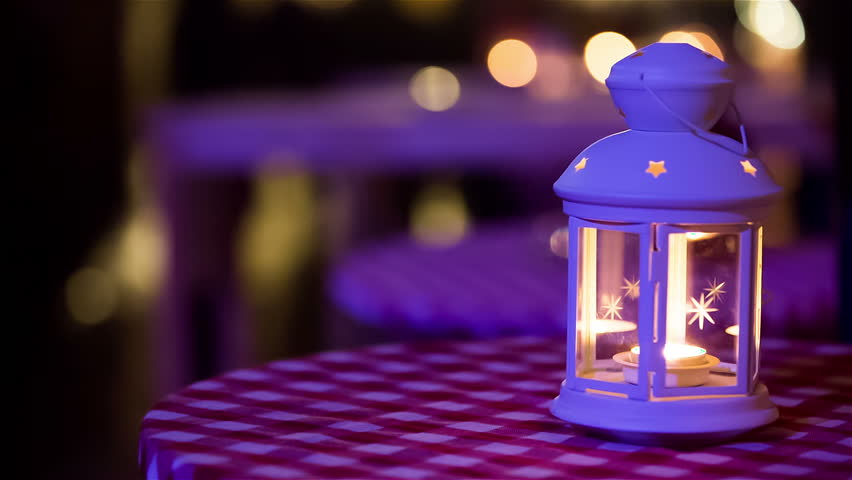 Lantern with candle close up. White lantern with stars and burning candle inside on table outside at night.