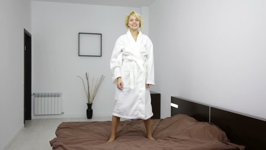 woman in bathrobe dancing on bed, young pretty girl happy smile - HD stock footage clip