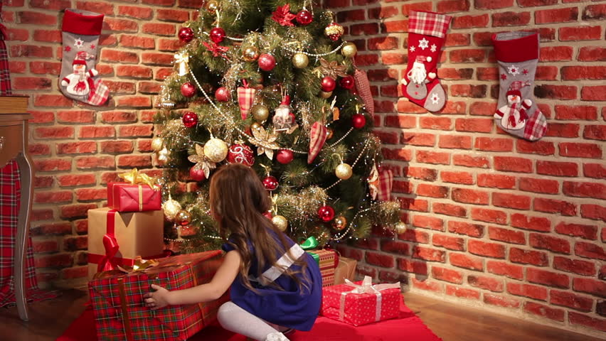 Little Girls Take Presents From Underneath The Christmas
