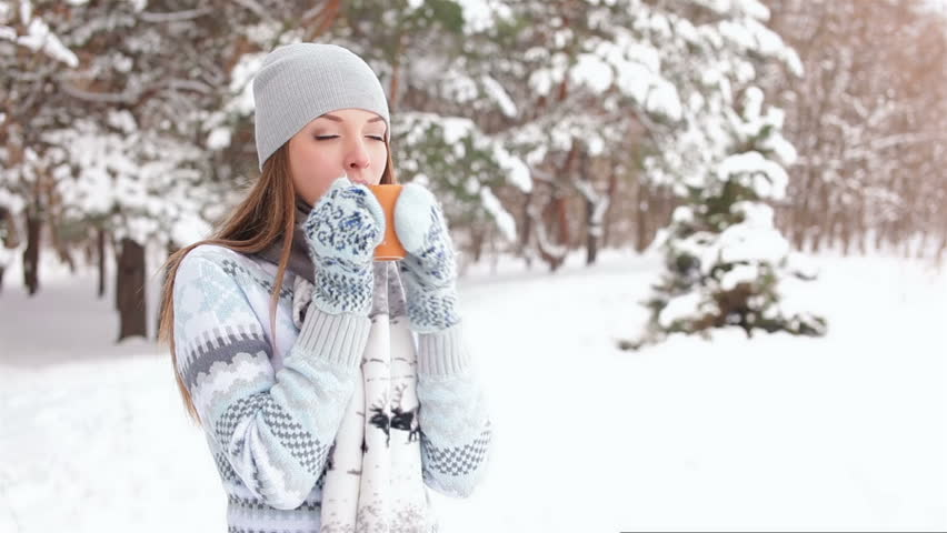 Girl drinks coffee outdoors in winter forest - HD stock footage clip