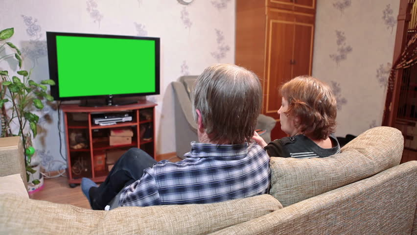 Mature parents watching tv show on green screen tvset while two children playing near | Shutterstock HD Video #8595943