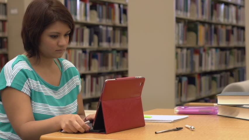 Female using tablet in library - HD stock footage clip