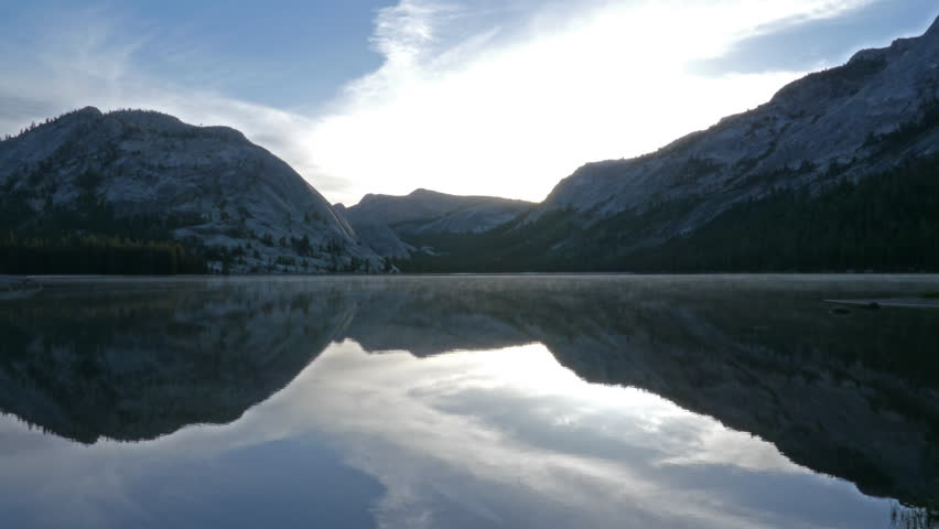 Time lapse footage with zoom in motion of sunrise at reflective lake along Tioga Pass in Yosemite National Park, California