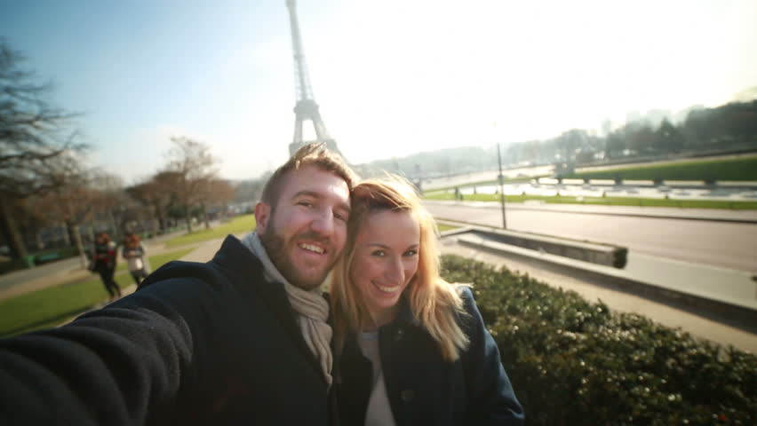 Happy cheerful couple in Paris in front of the Eiffel tower on the Champs de Mars taking a selfie using a mobile phone.  Winter and clear sky day in Paris.