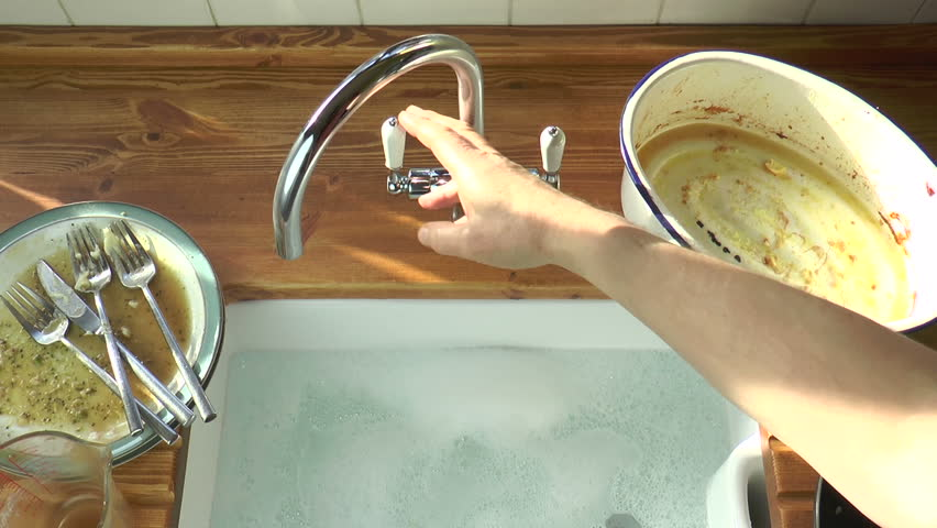 Dirty dishes are placed into a Belfast sink full of hot, soapy water. - HD stock video clip