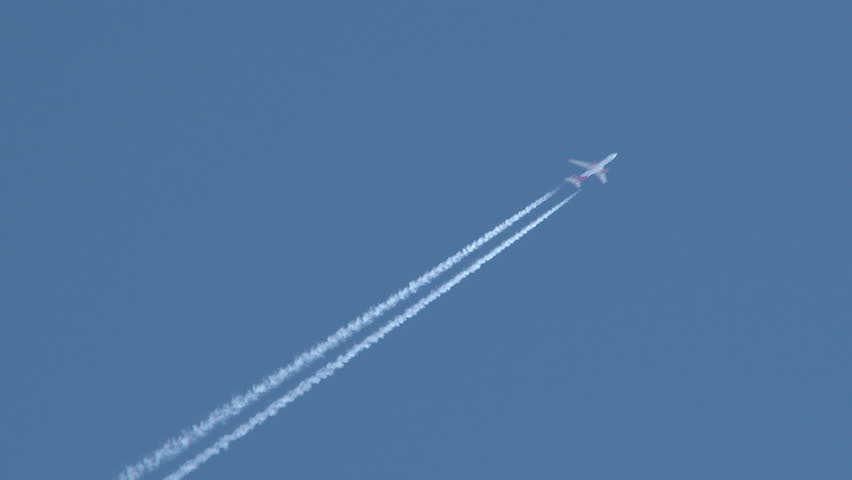 4K - Airplane flies overhead through frame on clear, blue sky day leaving behind vapor trail jet contrails. - 4K stock footage clip