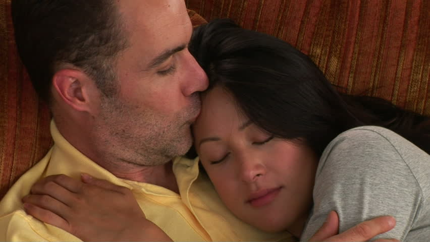 Romantic young couple on couch caressing and kissing - HD stock video clip