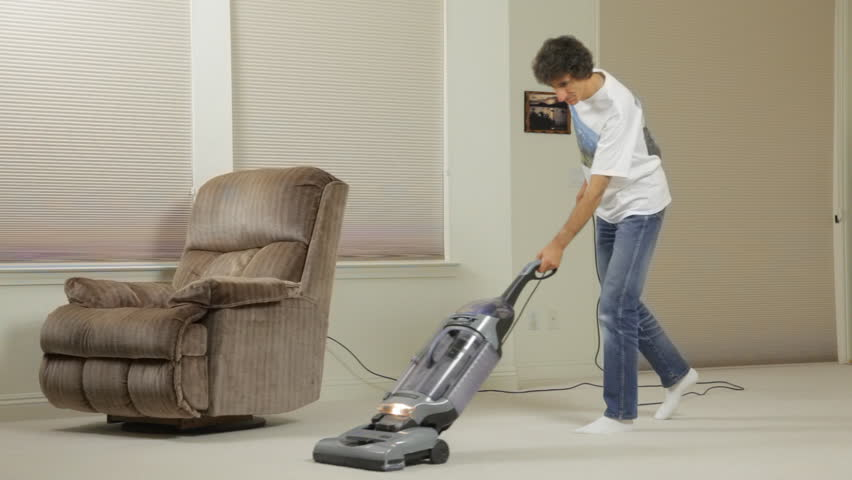A Man Using An Upright Vacuum Vacuums A Carpet Stock