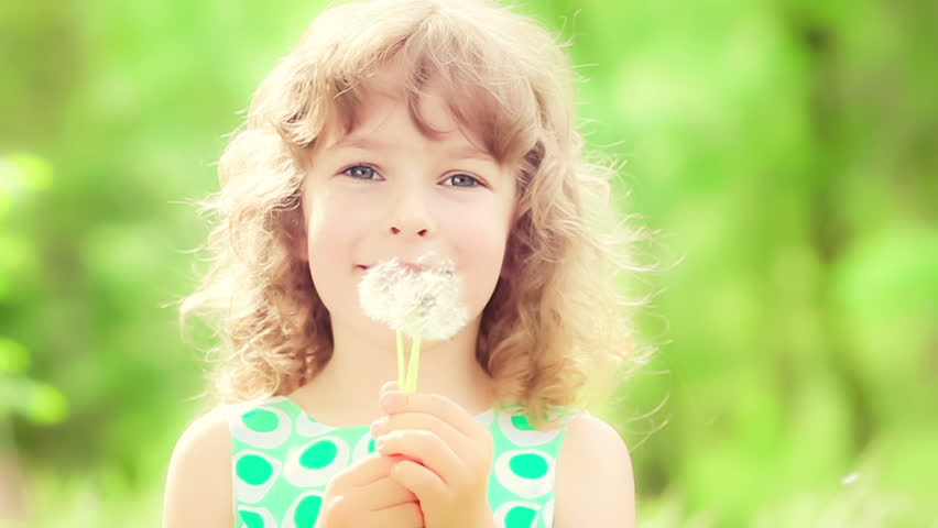 Happy child blowing dandelion flower outdoors. Smiling kid playing in spring park. Slow motion | Shutterstock HD Video #8777581