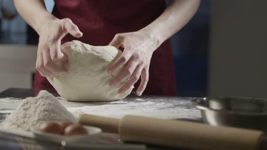 Man chef kneads the dough