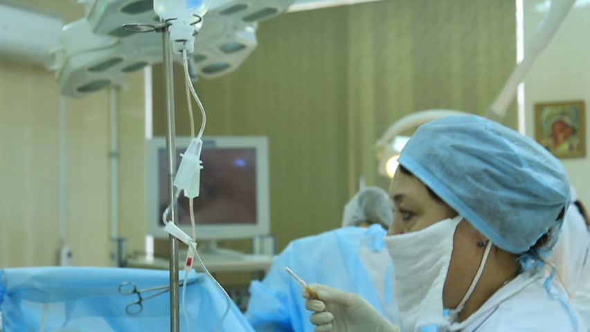 Oncosurgery: Medical personnel adjusts a dropper during surgery