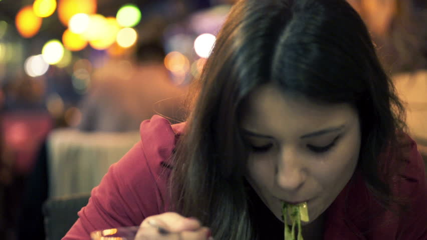 Young beautiful woman eating pasta in restaurant at ngiht
