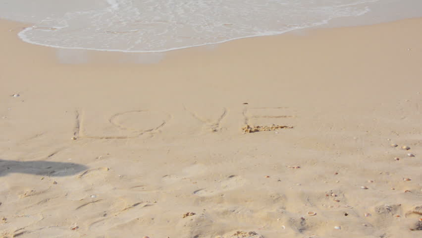 Mans feet walking on the written word love in the sand - HD stock footage clip
