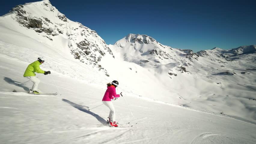 couple skiing on ski piste side view