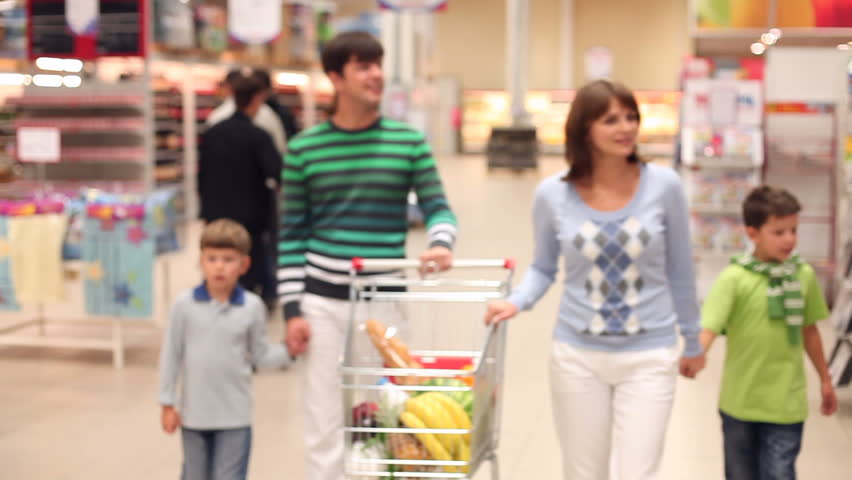 A family of four rolling a trolley with products along the supermarket, looking around and talking  | Shutterstock HD Video #885949
