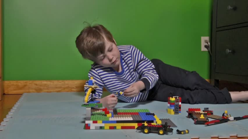 Tracking Dolly Shot Of Young Boy Playing With Lego On