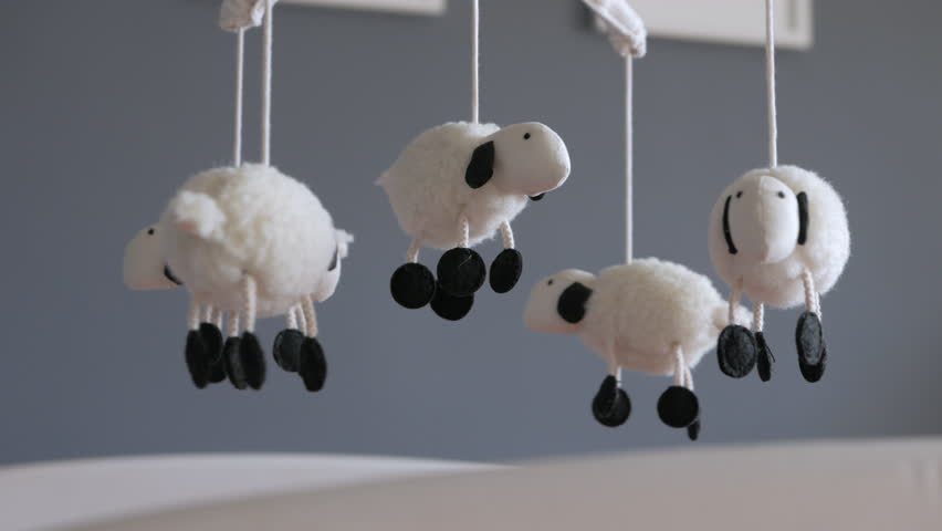 Lamb Nursery Mobile Spinning Above Baby Crib Close Up