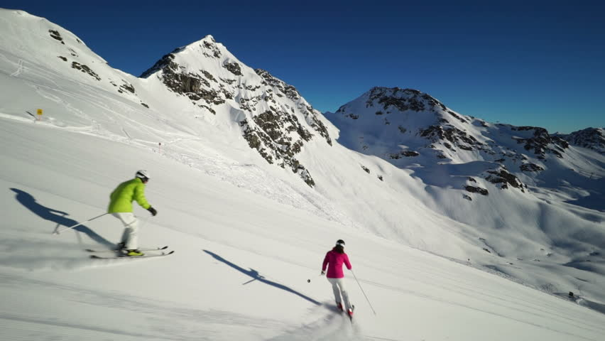 two skiers carving on empty ski piste
