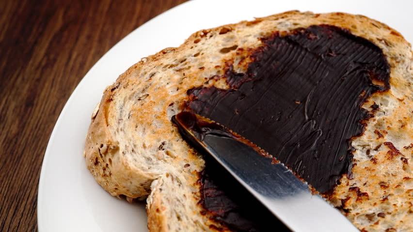 Spreading Australian Vegemite on whole wheat toast in slow motion