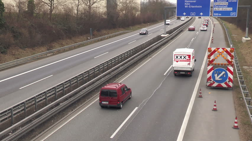 Wiesbaden, Germany - February 18, 2015: Construction site and warning sign on German highway A66 nearby Wiesbaden-Biebrich. High-angle view, passing cars - HD stock video clip