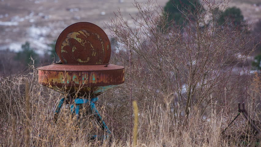 Rusty old farm equipment in grass. Close up of rusty farm equipment in overgrown dried grass on a sad day. - HD stock footage clip
