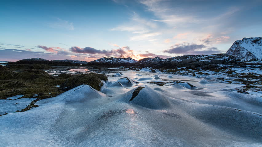 Frozen rock pools and seaweed in panning winter coastal scene from Norway