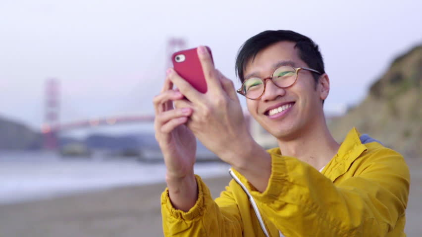 Multi-Ethnic Man Smiles And Takes A Selfie With His Smart Phone In Front Of Golden Gate Bridge