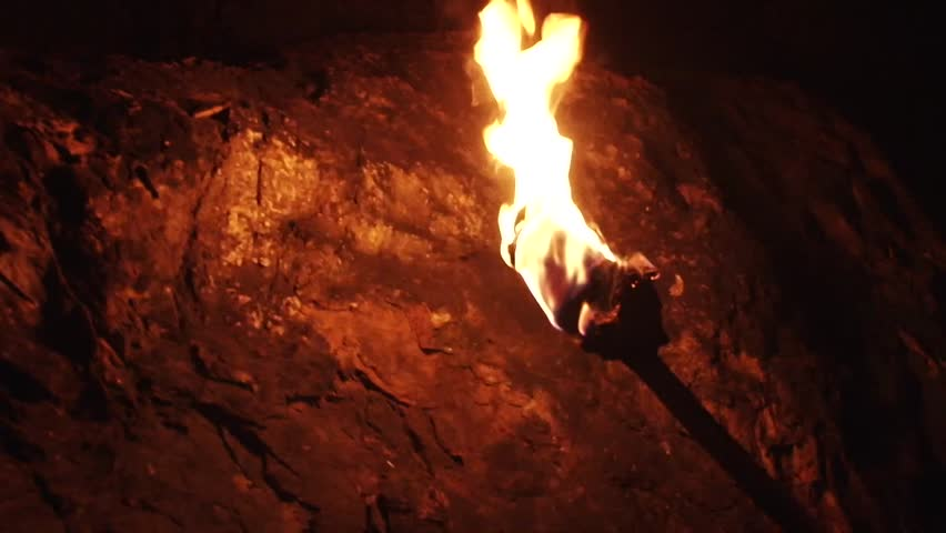 A burning wood made primitive torch, with strong flame, held in hand by a man. Good for religious, primordial times, undergorund worlds, speology, archeology, exploring or mistery, secrets scenes.