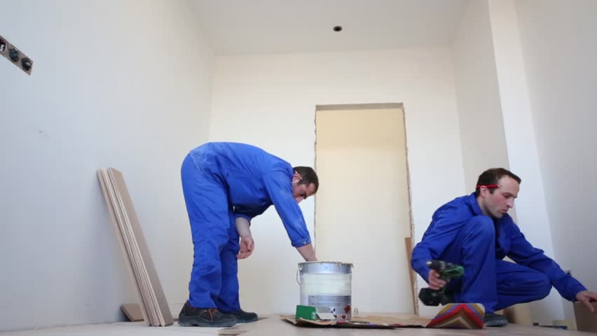 Installation of parquet - one worker drill holes in the board, the other smears glue on the floor | Shutterstock HD Video #8927926