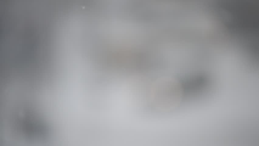 Close Up Of Snow Falling On Blurry Grey And White