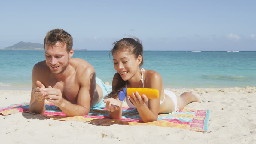 Beach Couple Sun Tanning Putting Sunscreen Suntan Lotion ...