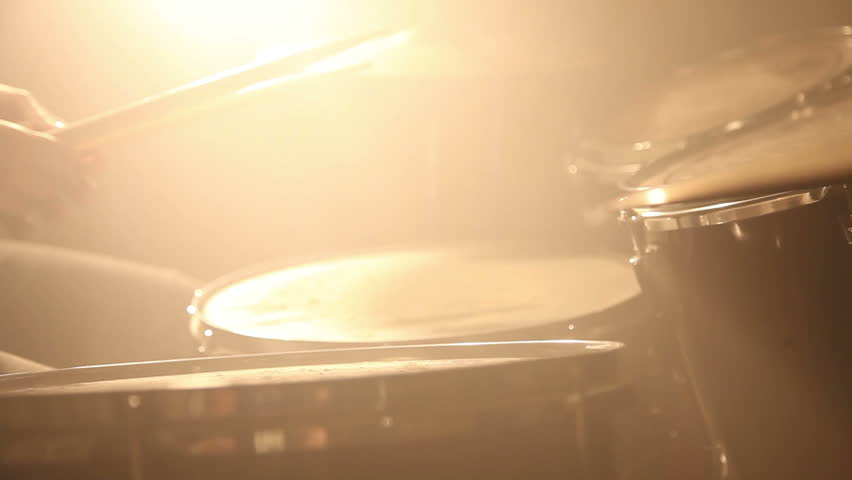 Close up of drums perfused with dust for special effect hit by unrecognizable guy